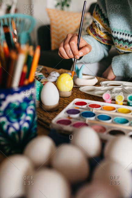 Unrecognizable person in sweater covering fresh chicken eggs with yellow paint while preparing for Easter celebration