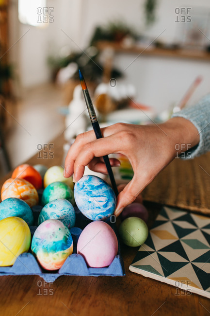 Unrecognizable person with brush arranging colorful eggs on carton on table while preparing for Easter celebration at home