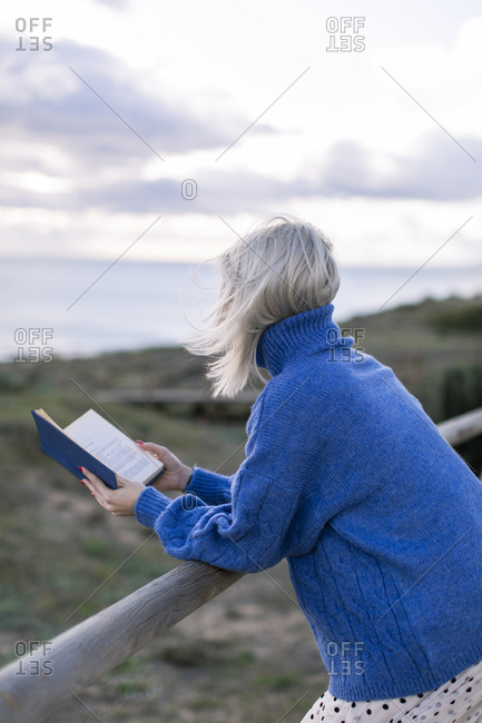 Side view of unrecognizable young female in blue sweater leaning on wooden fence and enjoying favorite poetry while spending time at seaside
