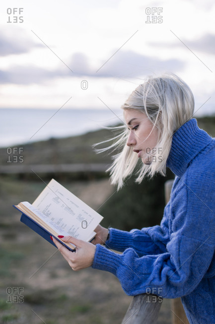 Side view of young female in blue sweater leaning on wooden fence and enjoying favorite poetry while spending time at seaside