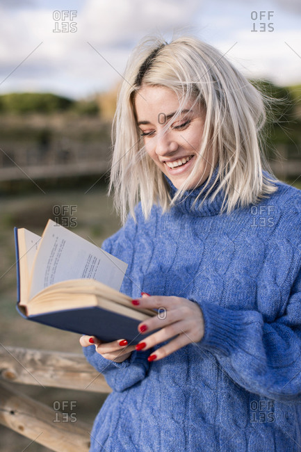 Cheerful young blonde female in warm blue sweater leaning on wooden fence and reading book while spending spring day in countryside