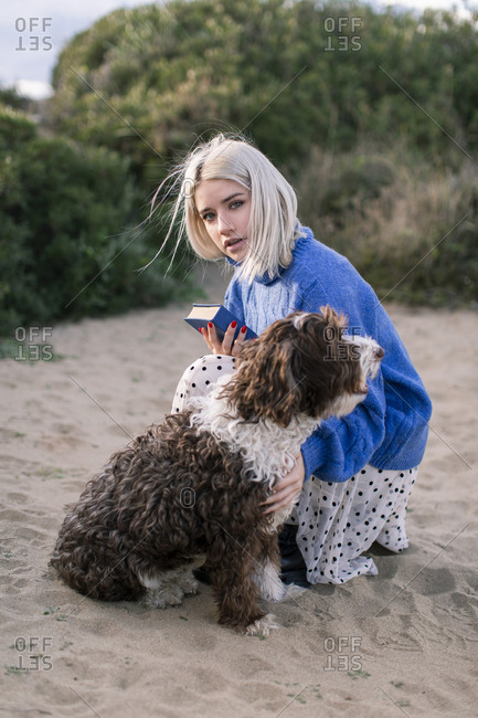 Side view of young woman looking at camera in casual sweater and skirt holding book and stroking adorable curly dog while spending free time on sandy beach with green plants in background