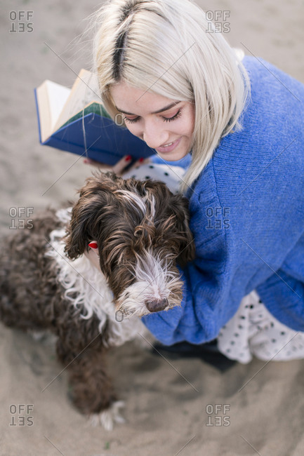 From above happy young female in casual sweater and skirt holding book and stroking adorable curly dog while spending free time on sandy beach