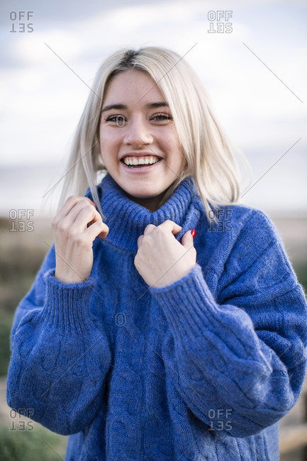 Joyful cheerful young blonde female in blue knitted sweater looking at camera and laughing while standing against blurred background of sea coast