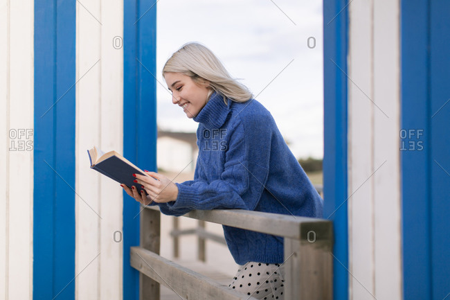 Happy young female in warm sweater and skirt leaning on wooden fence with open book reading against white and blue striped wall