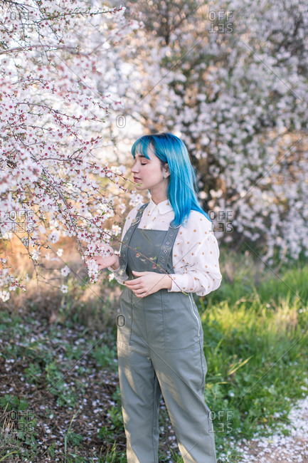 Young stylish female with long blue hair looking away wearing trendy overall enjoying fragrance of blooming tree while standing in spring garden