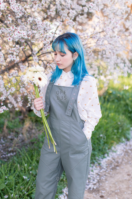 Modern trendy female with blue hair holding and looking at bouquet of fresh flowers while standing in blooming spring garden