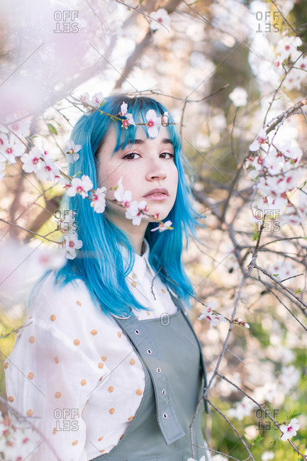 Young stylish female with long blue hair looking at camera wearing trendy overall enjoying blooming tree while standing in spring garden