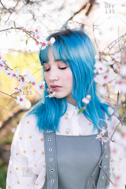 Young stylish female with long blue hair with closed eyes wearing trendy overall enjoying fragrance of blooming tree while standing in spring garden