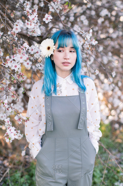 Millennial female model with white flower in blue hair dressed in trendy gray overall standing against blooming sakura tree in garden