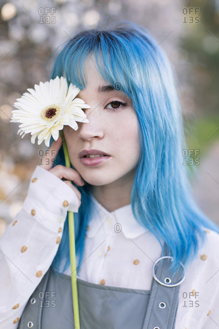 Modern trendy female with blue hair holding a fresh flower covering eye and looking at camera while standing in blooming spring garden