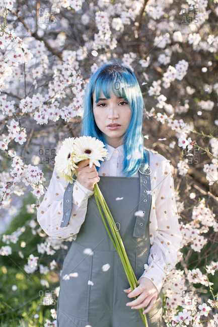 Modern trendy female with blue hair holding bouquet of fresh flowers and looking at camera while standing in blooming spring garden