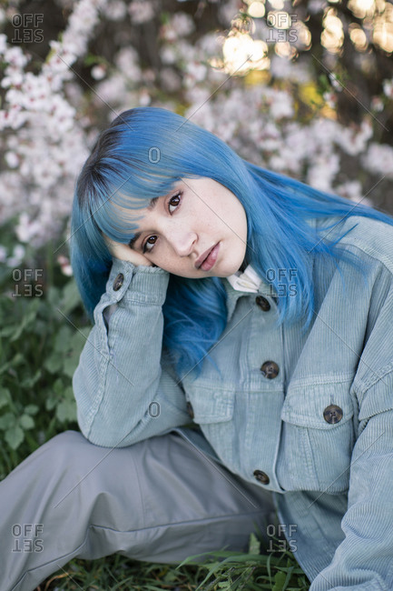 Sad millennial female model with blue hair in stylish outfit looking at camera thoughtfully while sitting on green grass near blooming tree in spring garden