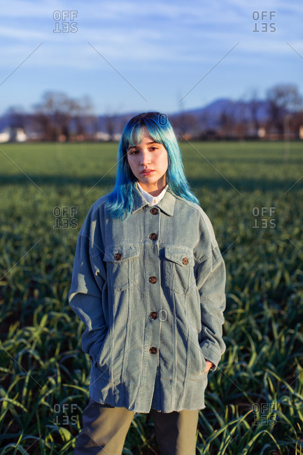 Thoughtful young female with blue hair looking at camera dressed in trendy jacket standing in green field in sunny evening