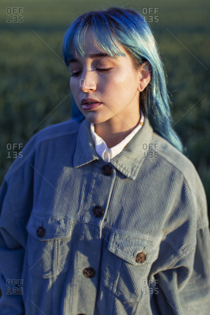 Upset pensive young female with blue hair dressed in trendy jacket standing in green field in sunny evening