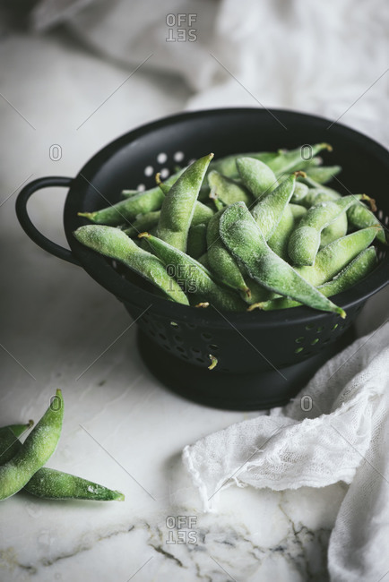 From above black colander with unripe soybeans for edamame dish preparation placed near gauze napkin on marble tabletop
