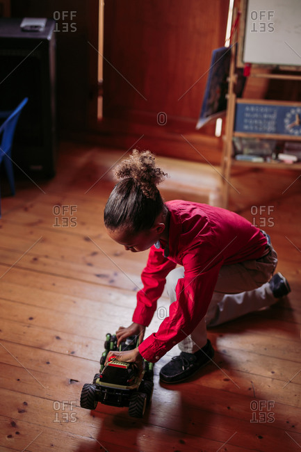 From above side view of ethnic child in casual clothes sitting on wooden floor and playing with toy car at home