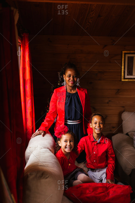 Cheerful young black female with cute laughing siblings in red clothes looking at camera while spending time together in cozy country house