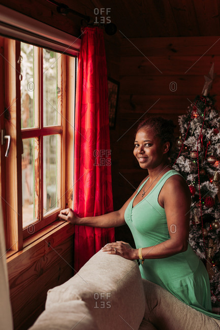 Side view of positive black female in casual dress looking at camera while standing near window in cozy wooden house with Christmas tree