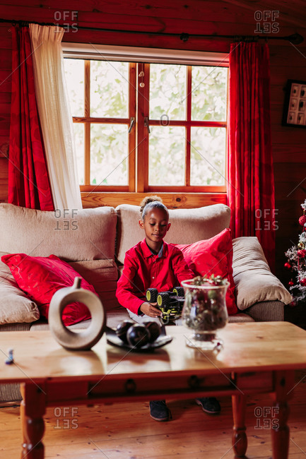 Satisfied black girl holding toy in hands and looking at camera while sitting on sofa near window in cozy living room with Christmas decoration