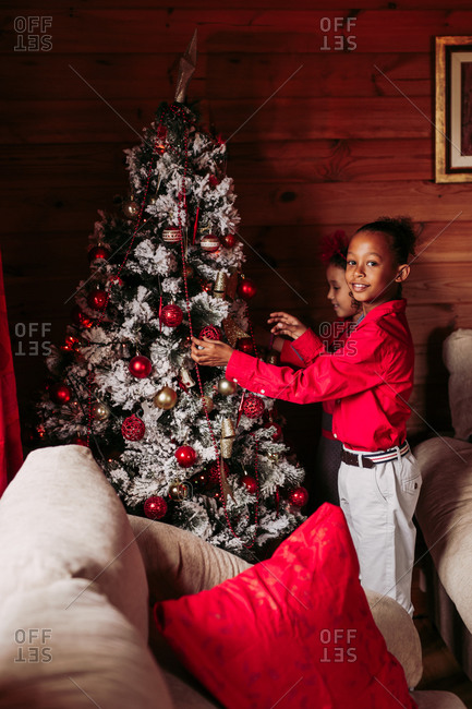 Side view of cute ethnic siblings in casual clothes decorating traditional Christmas tree in cozy wooden house