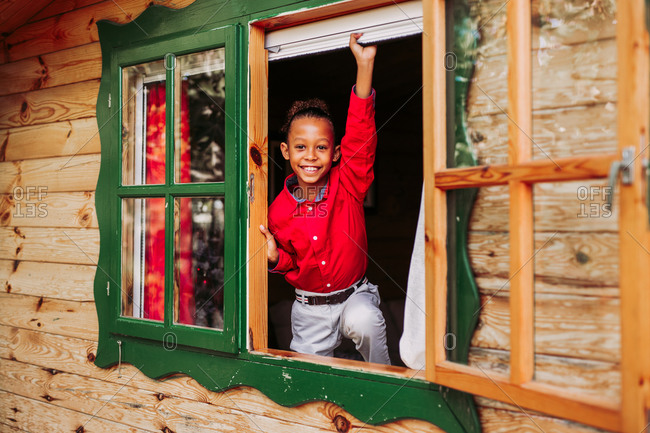 Cheerful black child in red shirt and white pants looking at camera through open window of rural wooden house