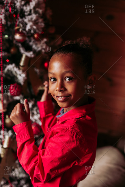 Side view of cheerful little black girl in red shirt looking at camera and smiling while standing near decorated Christmas tree at home