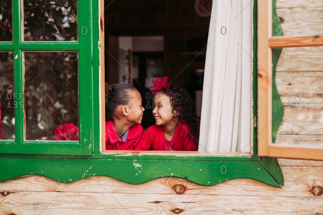 Cute black little siblings smiling through open window of wooden cabin
