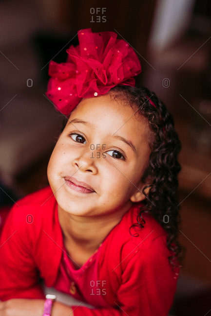 From above of cute little curly haired ethnic girl with red bow wearing red dress looking at camera and smiling against blurred background
