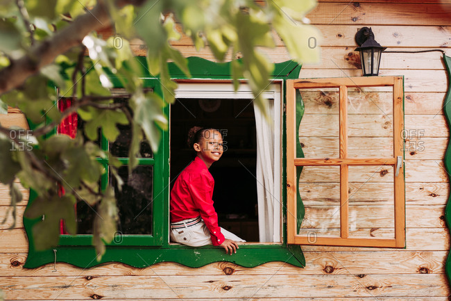 Cheerful black child in red shirt and white pants looking through open window of rural wooden house