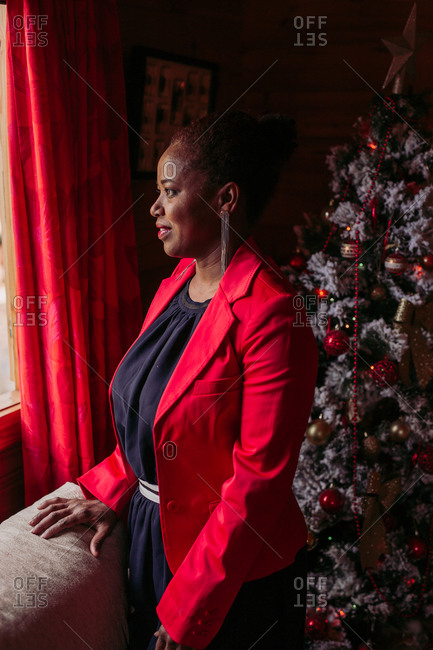 Side view of positive black female standing near window in cozy wooden house with Christmas tree