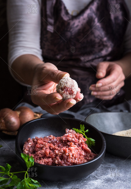 From above unrecognizable person wearing apron showing meatball to camera over bowls with minced meat and bread crumbs during lunch preparation