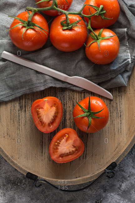 Halved and whole fresh tomatoes placed wooden board on rough gray table during food preparation in kitchen