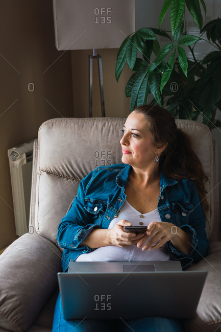 Mature woman with laptop browsing smartphone and looking away while sitting in armchair and working on remote project at home