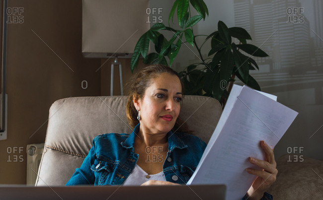 Mature woman reading paper while sitting in armchair and doing remote job on laptop near window at home