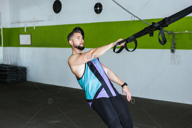 Side view of young muscular man in sportswear training with elastic resistance bands during intense workout with friend in modern gym
