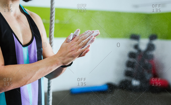 Side view of crop anonymous male athlete putting chalk powder on hands while standing next to rope and preparing for training in gym