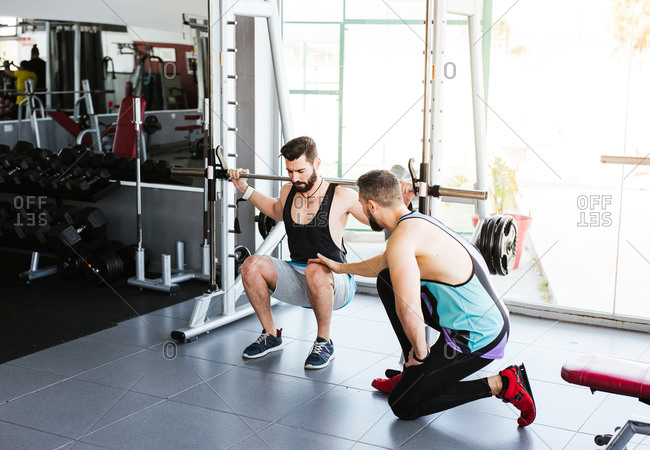 Powerful determined sportsman doing exercise with barbell at squat rack during weightlifting training with personal coach in modern gym
