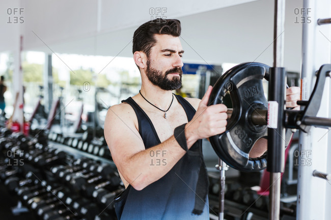 Muscular bearded man in sportswear standing near squat rack and putting weight disk on barbell while preparing for weightlifting training in modern gym