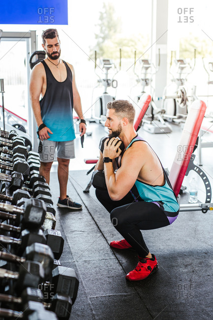 High angle of calm confident adult man in activewear performing single leg squat exercise with dumbbell while leaning on bench against blurred interior and sports equipment in modern spacious fitness club