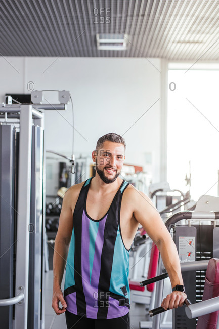 Muscular bearded man in sportswear looking at camera while standing with arms crossed and leaning on sports equipment in light contemporary gym