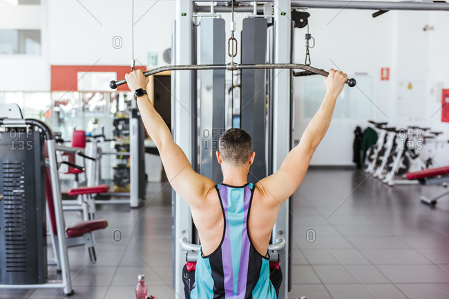 From above back view of unrecognizable sportsman in sports clothes performing exercise on weight machine against blurred interior of contemporary sport club