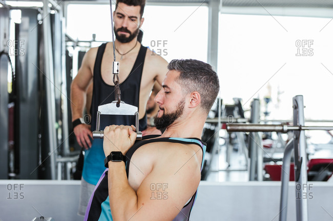 Confident instructor helping diligent client in sports clothes performing exercise on weight machine while standing against blurred interior of modern sport center