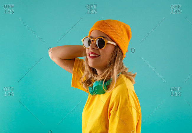 Side view of happy young cute female in yellow outfit and orange beanie looking away wearing sunglasses sunglasses against colorful turquoise background