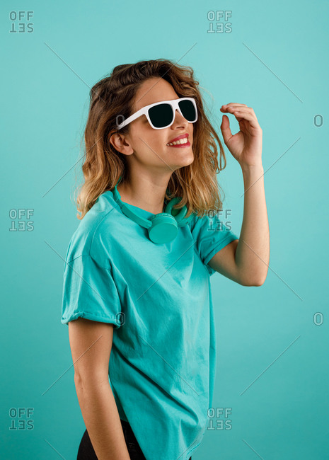 Side view of happy young woman in bright t shirt smiling looking away wearing sunglasses with headphones resting in her neck against turquoise background