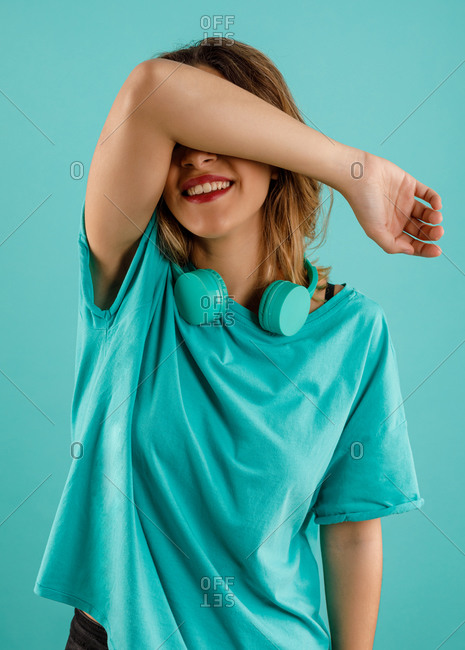 Happy young woman in bright t shirt smiling with arm over the face covering eyes with headphones resting in her neck against turquoise background