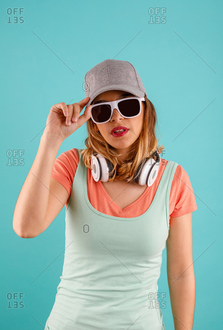 Young female in stylish sunglasses and cap touching headphones and looking at camera with headphones around her neck against turquoise background