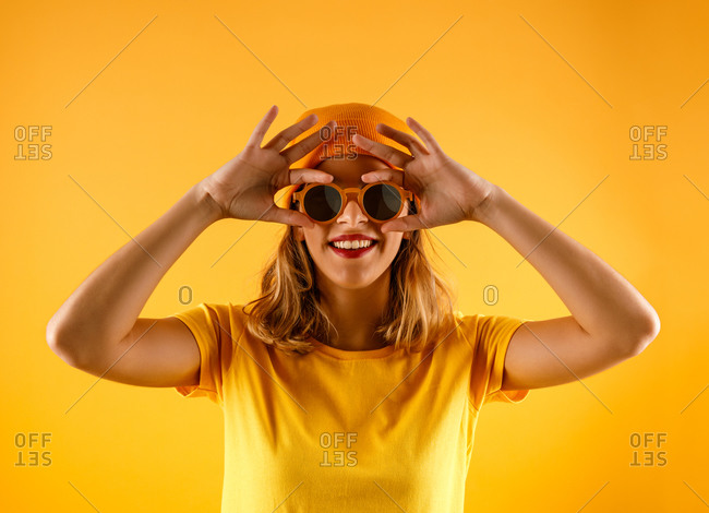 Happy young woman in bright clothes and stylish sunglasses smiling and looking at camera against orange background