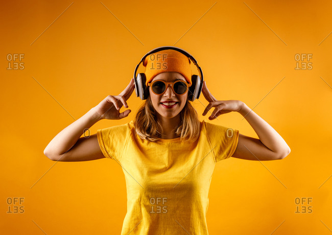 Happy young woman in bright clothes and stylish sunglasses smiling looking at camera while listening to music against orange background