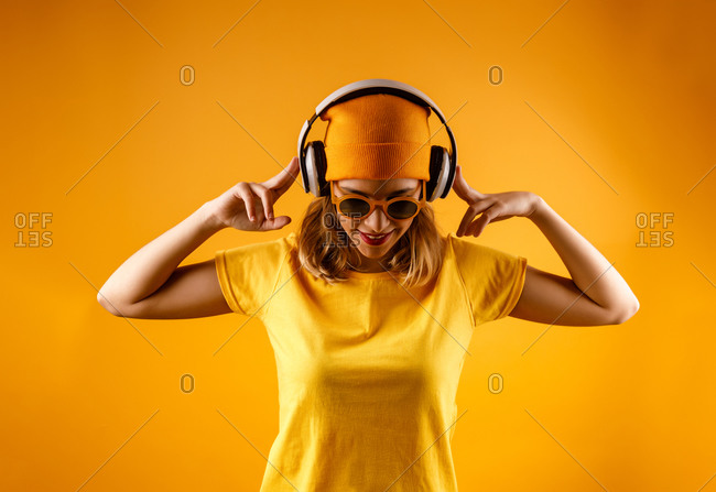 Happy young woman in bright clothes and stylish sunglasses smiling looking down while listening to music against orange background
